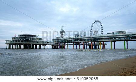 THE HAGUE, NEHTERLANDS - MAY 13, 2017: The Scheveningen Pier Strandweg, beach resort on North sea in The Hague Den Haag with Ferris wheel. The Hague, Netherlands
