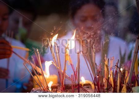 Burning incense and candles at thai buddhis celebration - Visakha Bucha Day