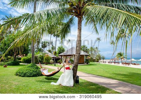 newlyweds relax in a tropical hotel park