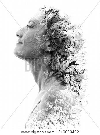 Double exposure. Paintography. Portrait of a beautiful young female model disappearing behind black ink painting on white background