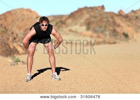 Workout outdoor runner. Man running taking a break from run outside in beautiful desert landscape. Fit young caucausian athletic model training for marathon outdoors.