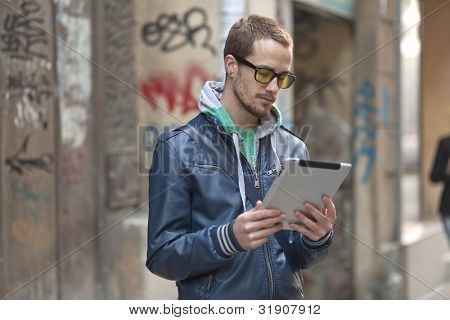 Young man with yellow glasses use iPad tablet computer on street, public space. Blurred background