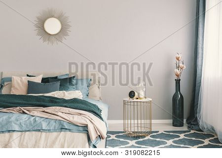 Clock And Flower In Fancy Vase On Nightstand Table Next To King Size Bedroom With Emerald Green And