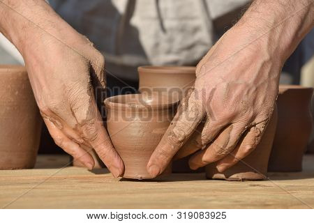 Pottery Male Ceramist Creates A Hand Made Clay Product. Process Of Rotation Of Potters Wheel, Hands