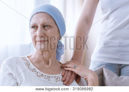 Elderly Woman Wearing Blue Headscarf, Suffering From Leukemia, Granddaughter Hand On Her Arm As A Si