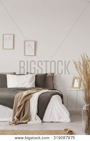 Graphics In Wooden Frames On White Empty Copy Space Wall In Bedroom With Comfortable Bed With Black