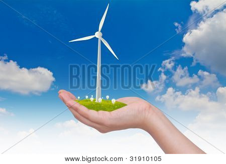 Wind turbines and light bulb on hand  over blue sky