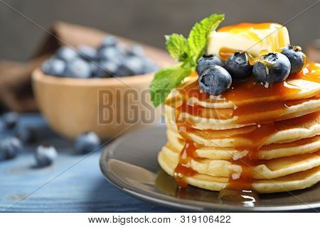 Delicious Pancakes With Fresh Blueberries, Butter And Syrup On Blue Wooden Table