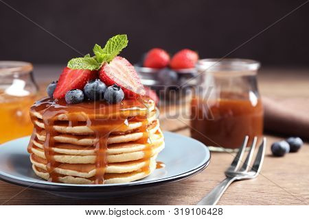 Delicious Pancakes With Fresh Berries And Syrup On Wooden Table