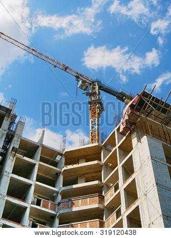 Concrete Building Under Construction. Construction Site. Two Tower Cranes Near Building.