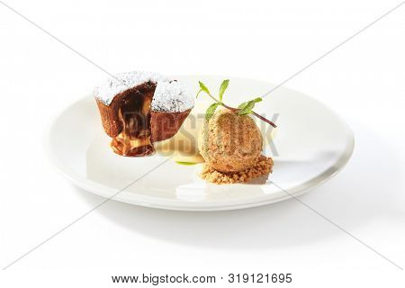 Whole hot chocolate fondant with ice cream ball and condense milk on white plate isolated. Restaurant dessert with fresh brownie, muffin or small chocolate cake with crunchy rind and mellow filling