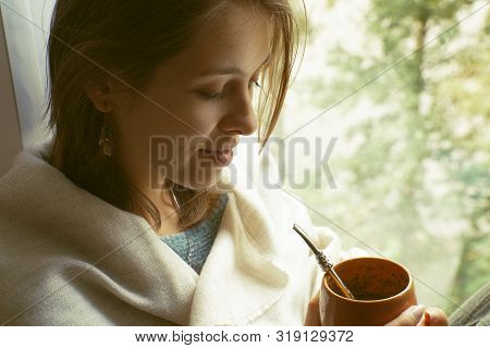 Girl Wrapped In Stole Sits By The Window And Holds Calabaza With Mate In Hands.
