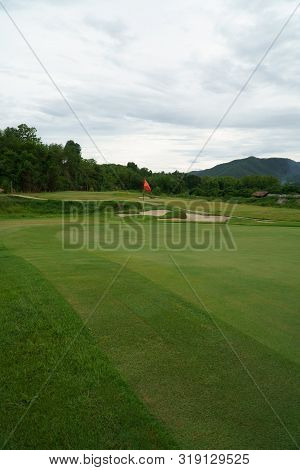 Red Flag And Green Grass Sand Bunker At The Beautiful Golf Course At The Mountain Side