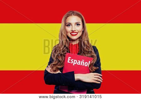Spain. Happy Student Girl With Red Book Against The Spanish Flag Background. Travel And Learn Spanis