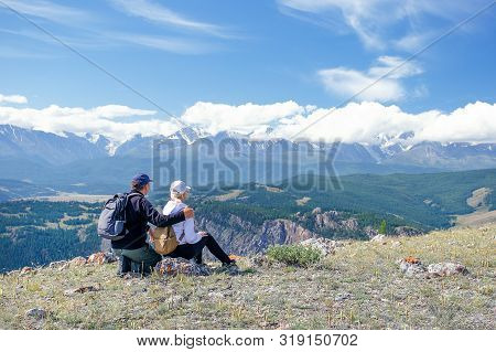 Couple Travelers Man And Woman Sitting On Cliff Relaxing Mountains And Enjoying Valley View.  Happy