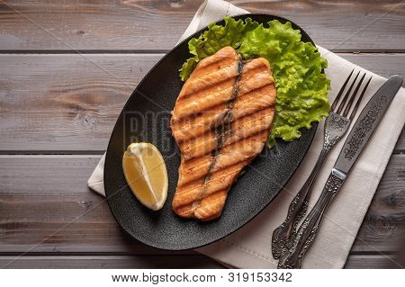 Homemade Grilled Salmon Steak On Lettuce Leaves. On A Plate On A Linen Napkin With A Knife And Fork.
