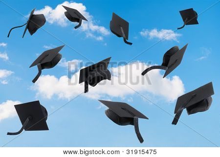 Graduation mortar boards thrown into a blue sky