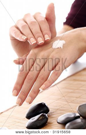 Beautiful hands with cream over white background