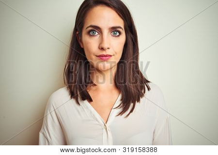 Young beautiful woman wearing casual shirt standing over white isolated background with serious expression on face. Simple and natural looking at the camera.