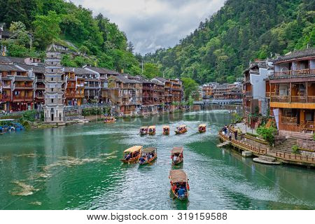 poster of Chinese tourist attraction destination - Feng Huang Ancient Town (Phoenix Ancient Town) on Tuo Jiang River with Wanming Pagoda tower and tourist boat. Hunan Province, China