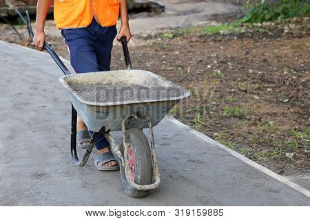 Worker Carries A Wheelbarrow With The Ground. Man With Cargo, Concept Of Earthworks, Digging, Constr