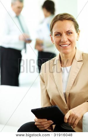 Smiling business woman looking at camera in working environment