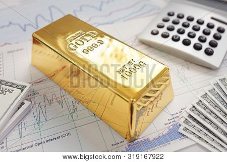 Gold ingot resting on a stocks and shares graph representing investment or banking