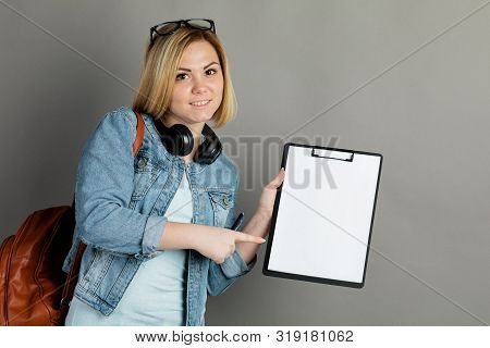 A Student With A Folder For Writing. On A Gray Background
