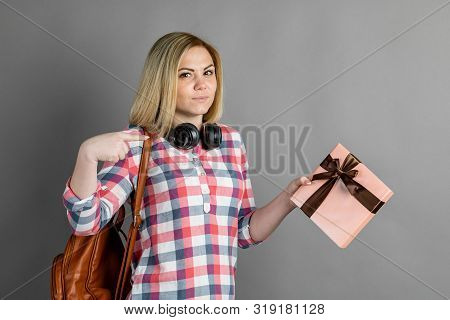 Studio Portrait Of A Cute Blond Girl, A Student, In A Plaid Shirt Looking At A Gift / A Pleasant Sur