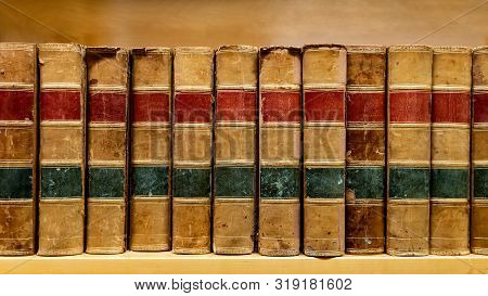 Antique Leather Cover Books On Wooden Bookshelf In University Public Library. Reading Philosophy Or