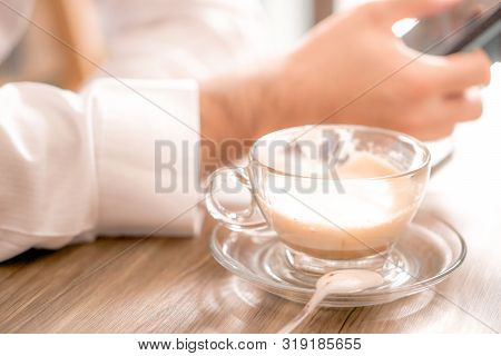 Coffee And Cafe Concept - Hot Latte Coffee Glass Cup On Wood Table With Business Man Seeing Socail M