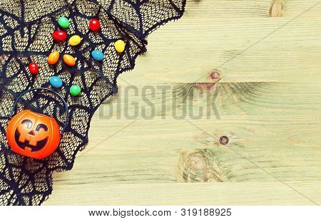 Halloween background. Spider web, cobweb lace and smiling jack decorations - Halloween tiny bag and candies as the symbols of Halloween on the light wooden background, festive Halloween concept