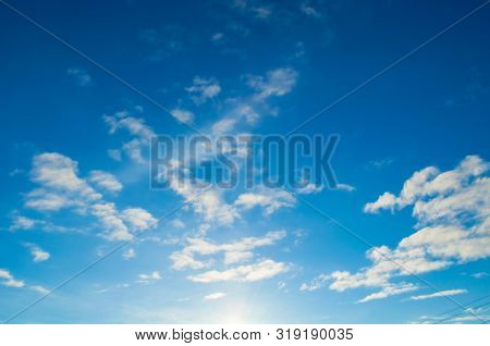 Blue dramatic sky background - picturesque bright clouds lit by sunlight. Vast sky landscape panoramic scene, blue sky view