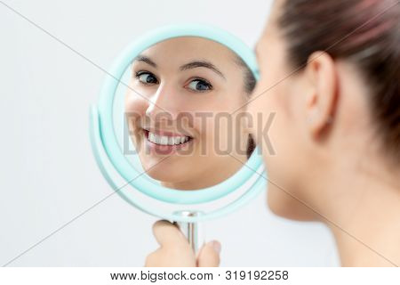 Close Up Portrait Of Young Woman Looking In Mirror At Herself. Girl With Healthy White Teeth Holding