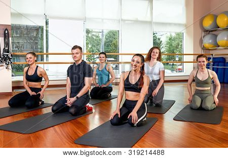 Happy Multiracial Group Of Young, Smiling Beautiful Girls And Panes In Sportswear, Doing Yoga Exerci