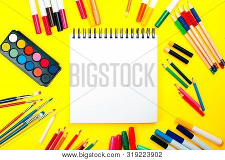 School Supplies On Yellow Background And Note Book With Copy Space. Back To School Concept.
