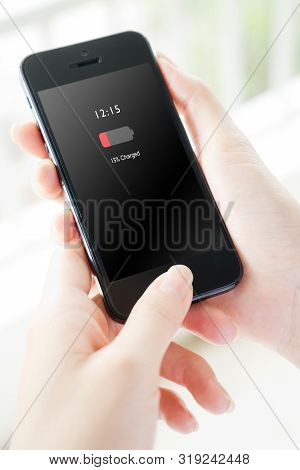 Female hand holding mobile phone with low charged battery screen
