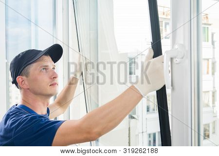Master Puts A New Double-glazed Window In A Plastic Window
