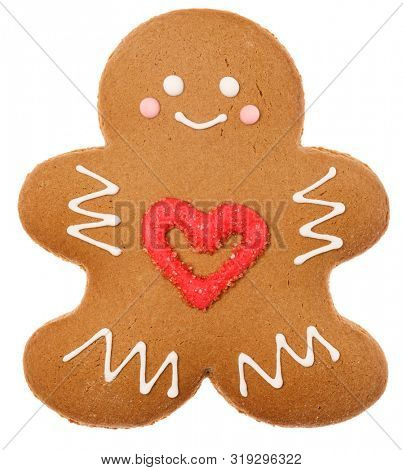 Christmas Gingerbread man sugar cookie in humanoid shape with red heart icing decoration isolated on white background