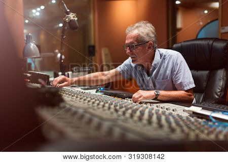 Male middle aged recording engineer in a recording studio sitting at a multi channel console