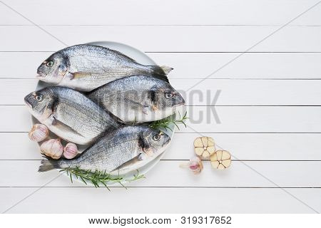 Four Fresh Royal Dorades On Dish On White Wooden Background. Healthy Food Concept. Top View, Copy Sp