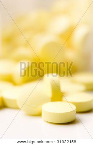 Yellow pills over white macro shot