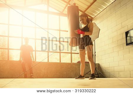 Sexy Fighter Girl In Gym With Boxing Bag, Female Boxer Resting After Punching A Boxing Bag In Gym