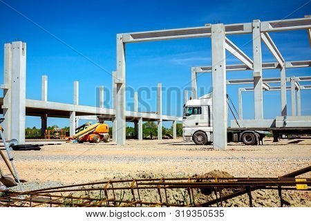 Truck With Trailer Is Transporting Long And Heavy Concrete Beam To Construction Site For Industrial
