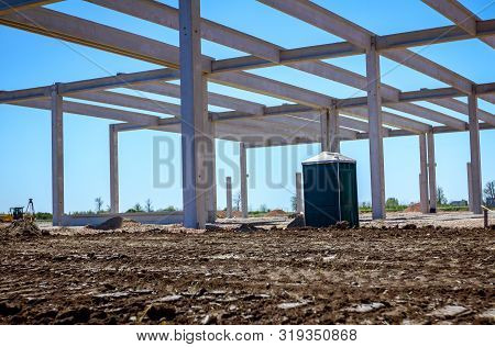Concrete Skeleton Of Unfinished New Edifice And Public Lavatory For Workers Is Placed At Constructio