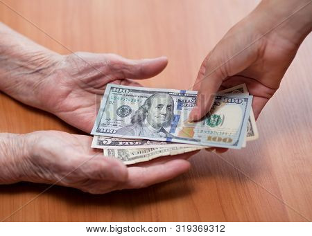 An Elderly Man Takes Money From The Hands Of A Young Girl. Financial Assistance Concept. Senior Citi