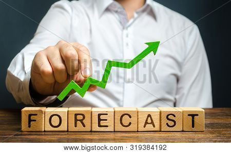 Man Holds Green Arrow Up Over Word Forecast. Prediction Of Profit Growth, Value Of Assets And Market