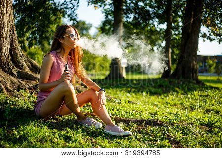 Vape Teenager. Young Pretty Sporty Caucasian Girl In A Pink Jumpsuit And Sunglasses Smoking An Elect