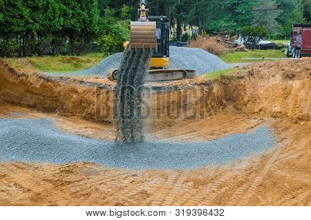 The Excavator Wheel During Backfilling Gravel Around The Foundation For A New Home Construction