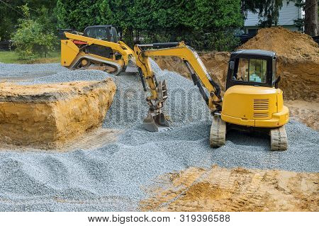 A Bulldozer On Wheels Backfill Of Foundation Work On The Construction To The Building Under Construc